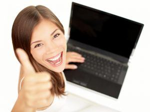 student smiling holding laptop