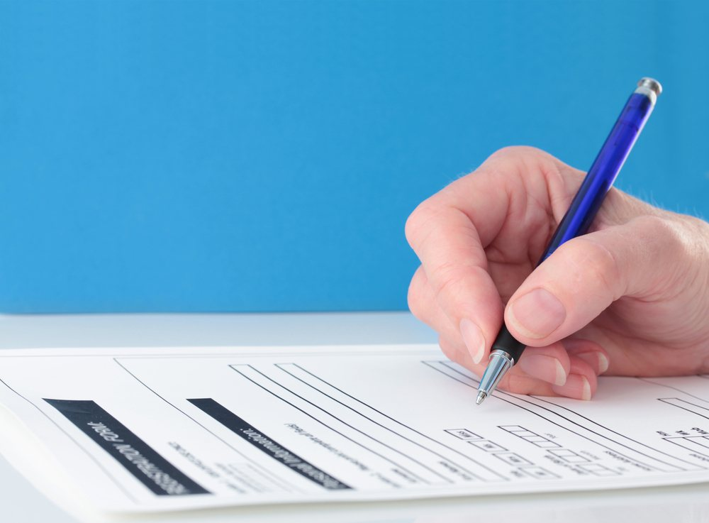 Photo of a person's hand with a pen in it as they fill out a college application