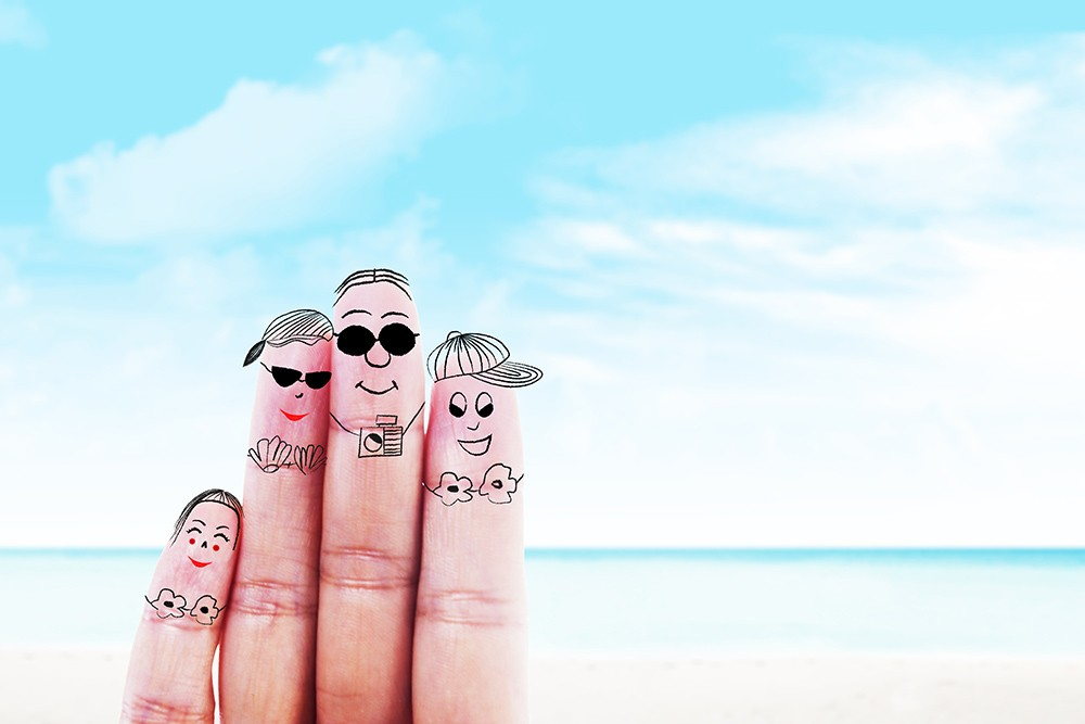 Faces drawn on the fingers of a hand  with a beach background. Add college visits to your summer plans!