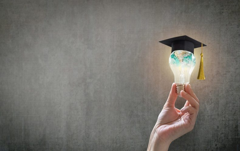 Innovative learning, creative educational study concept for graduation and school student success with world lightbulb on teacher chalkboard