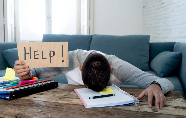 Young tired and stressed student working on his homework, masters feeling desperate and frustrated asking for help. In over Education, learning difficulties, finals exams and emotional stress concept.