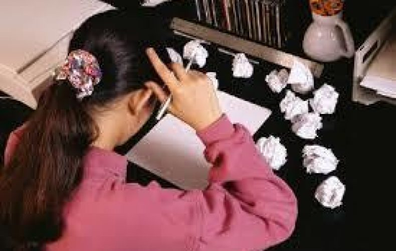 Girl who is looking down a a blank piece of paper with lots of crumpled paper around her. She is learning the don'ts of writing her college essay